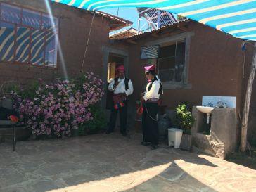 Uomini in abito tradizionale in procinto di scambiarsi coca